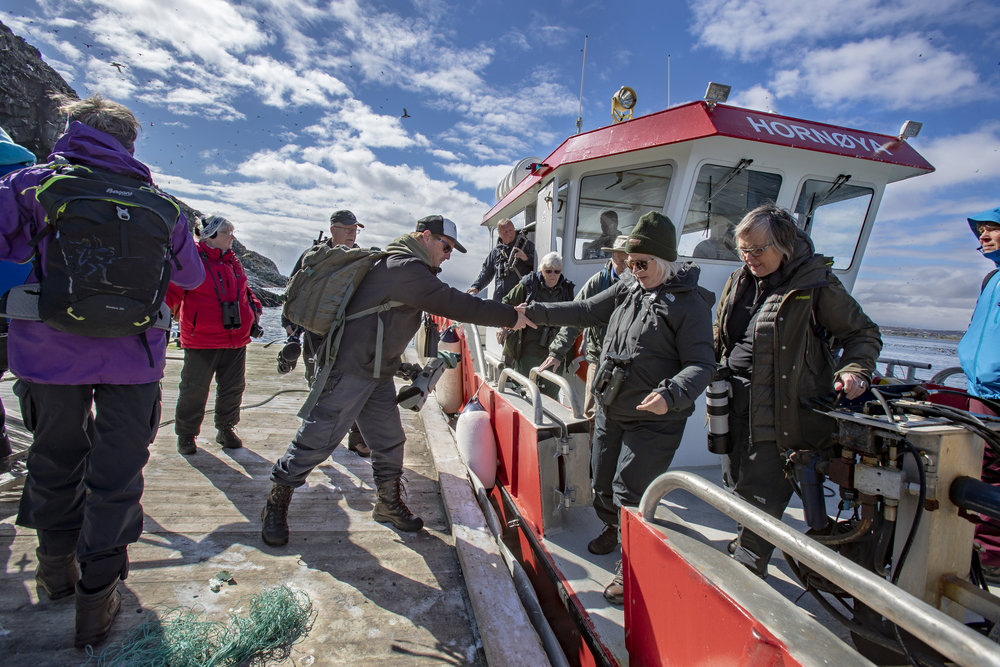 TURGRUPPER: Vardø Havnevesens båt er stor og stødig, noe mange eldre turister setter pris på. Anders Mæland hjelper sin utenlandske turgruppe på land.