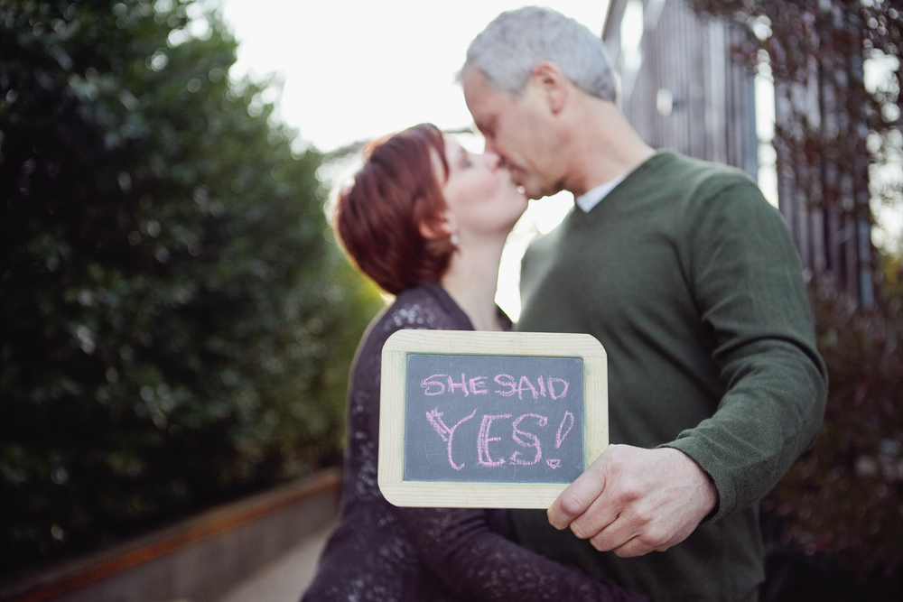 "Engaged couple holding ""she said yes"" sign"