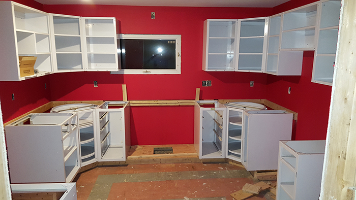 Cabinets during installation, on custom wooden plinth.
