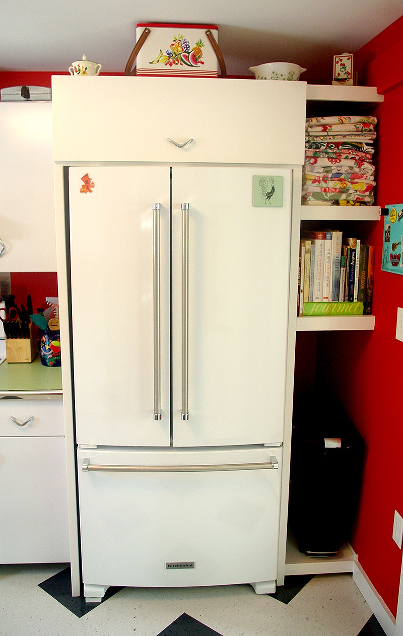 Custom fridge surround with tall appliance shelves and trash can storage.
