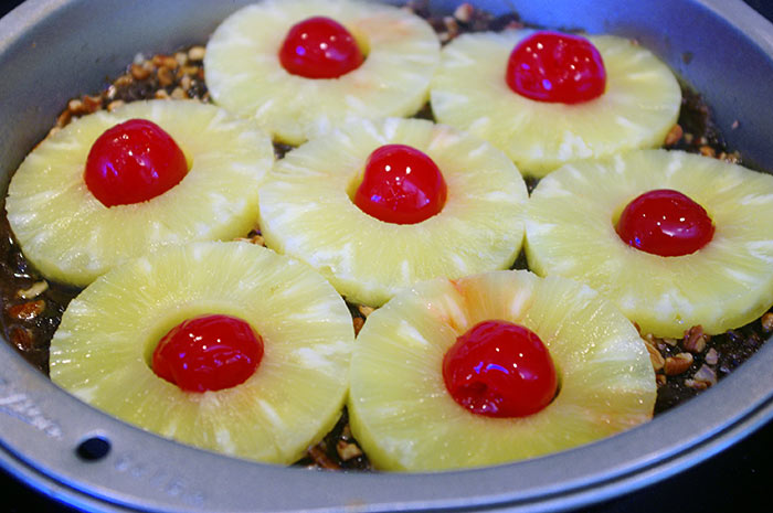 Pineapples and cherries arranged and ready for batter.