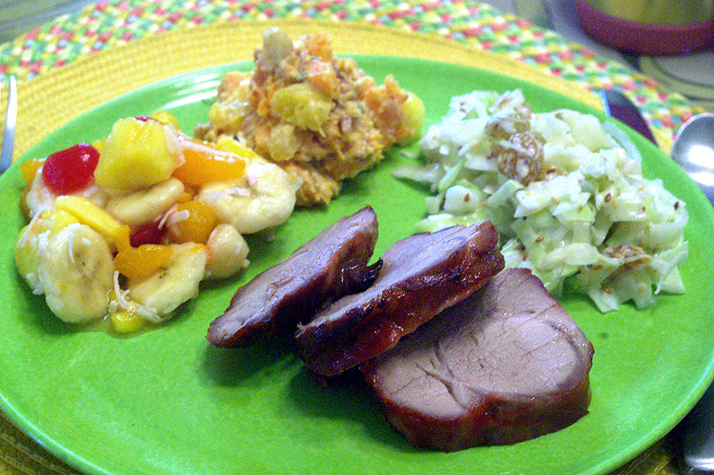 A plate with Ambrosia Polynesia, sweet potato salad, Surfer's Slaw and Lava Pork Tenderloin.