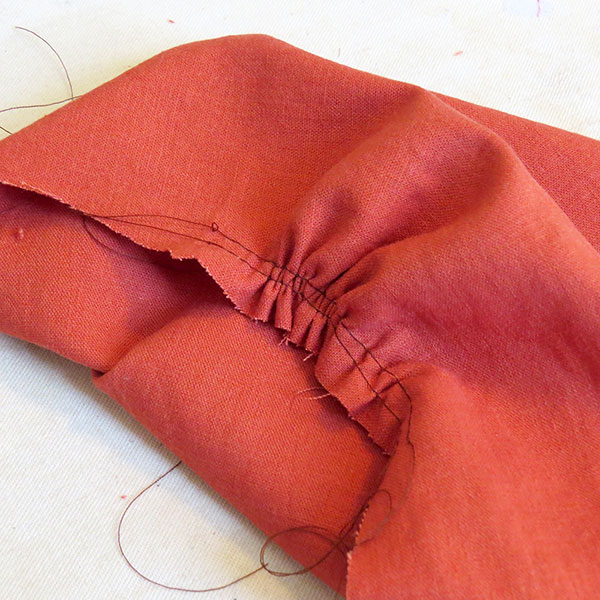 The rust-colored linen fabric, with some of the gathers for the upper bodice.