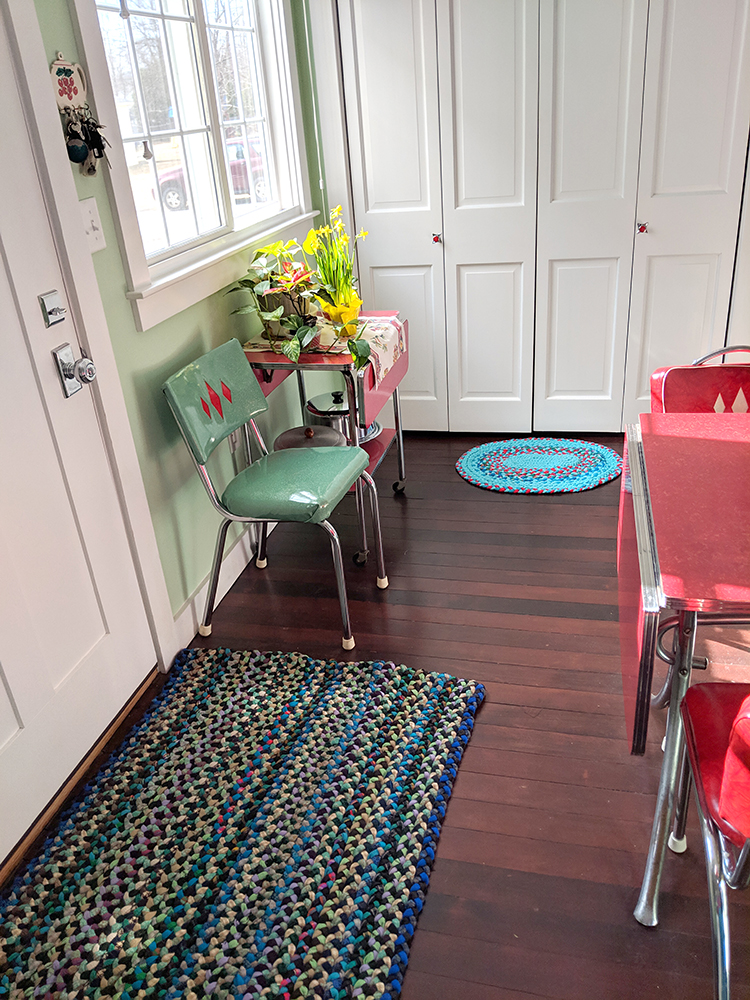 The room with both braided rugs.