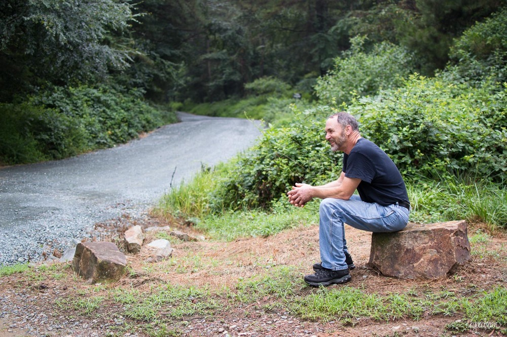 My dad pauses for a break on a rock by the gravel trail.