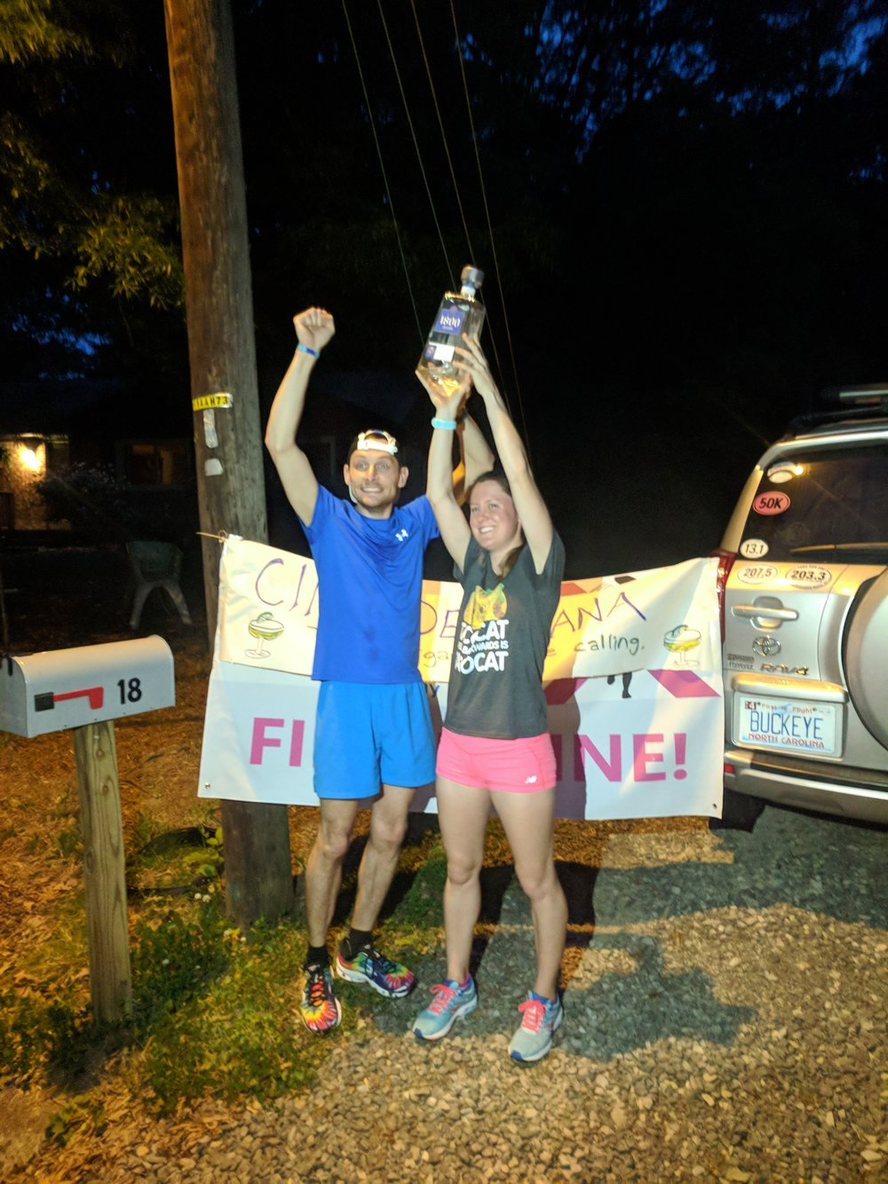 Nora and Jordan holding up the Margarita Mile trophy (aka the bottle with the leftover tequila)