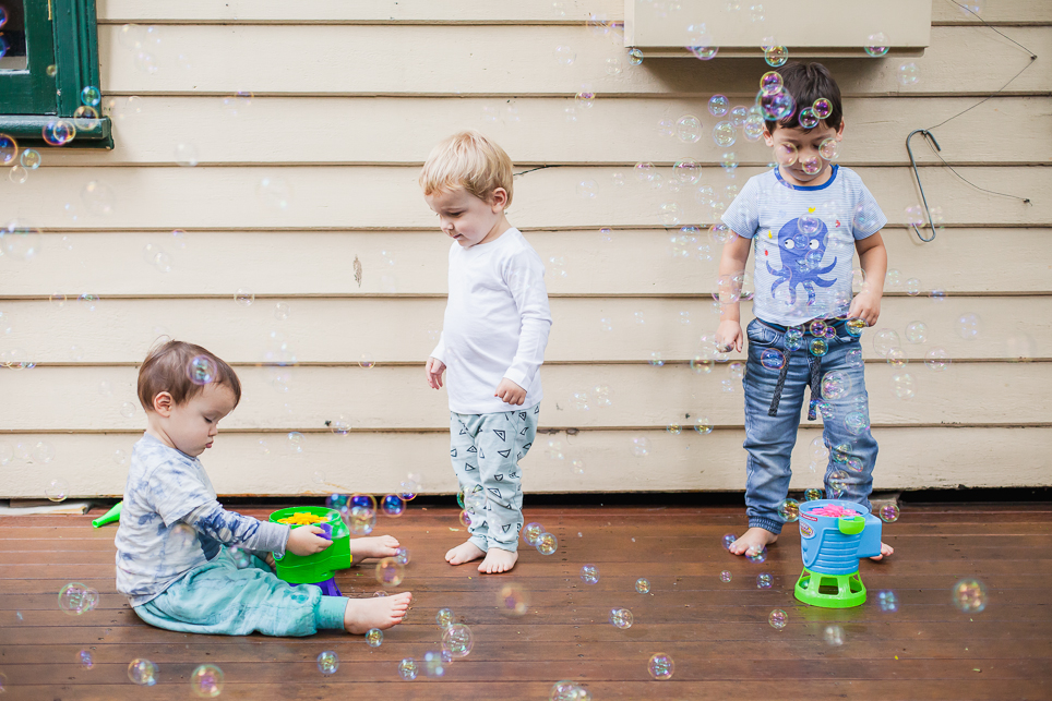 The boys playing together with the bubbles.