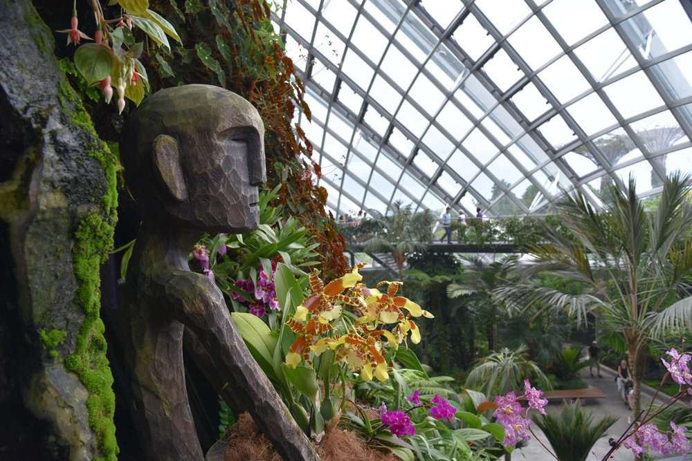 This figure has the perfect spot amidst the orchids to admire the Cloud Dome at Gardens by the Bay.