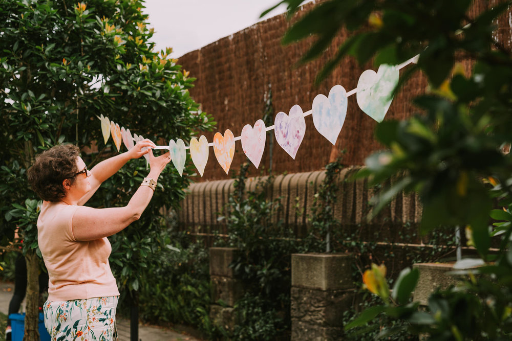 Behind the scenes as I hang strings of watercolour heart bunting to add a splash of colour and love to the garden setting. Photo by Angus Porter Photography