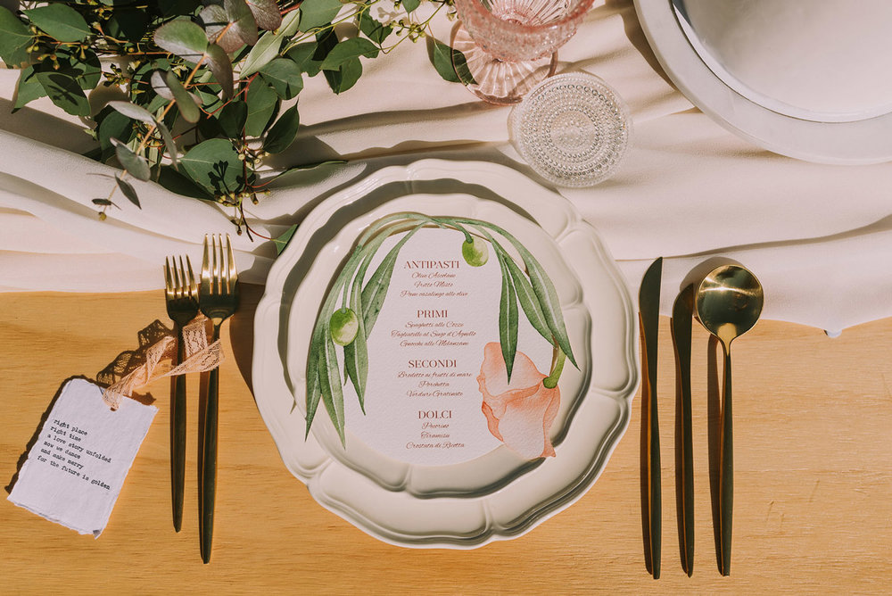 Bespoke hand-painted watercolour menu design inspired by Bella Vita of olive branches by ELK Prints for a wedding table. Photo by Angus Porter Photography.