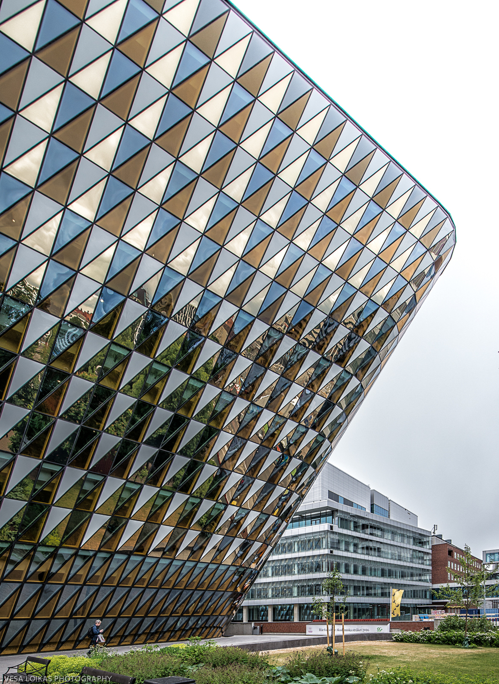 Leaning In - Karolinska Institutet New Lecture Hall | A university auditorium in a Stockholm suburb with a patterned glass facade that twists and leans over the adjacent street.