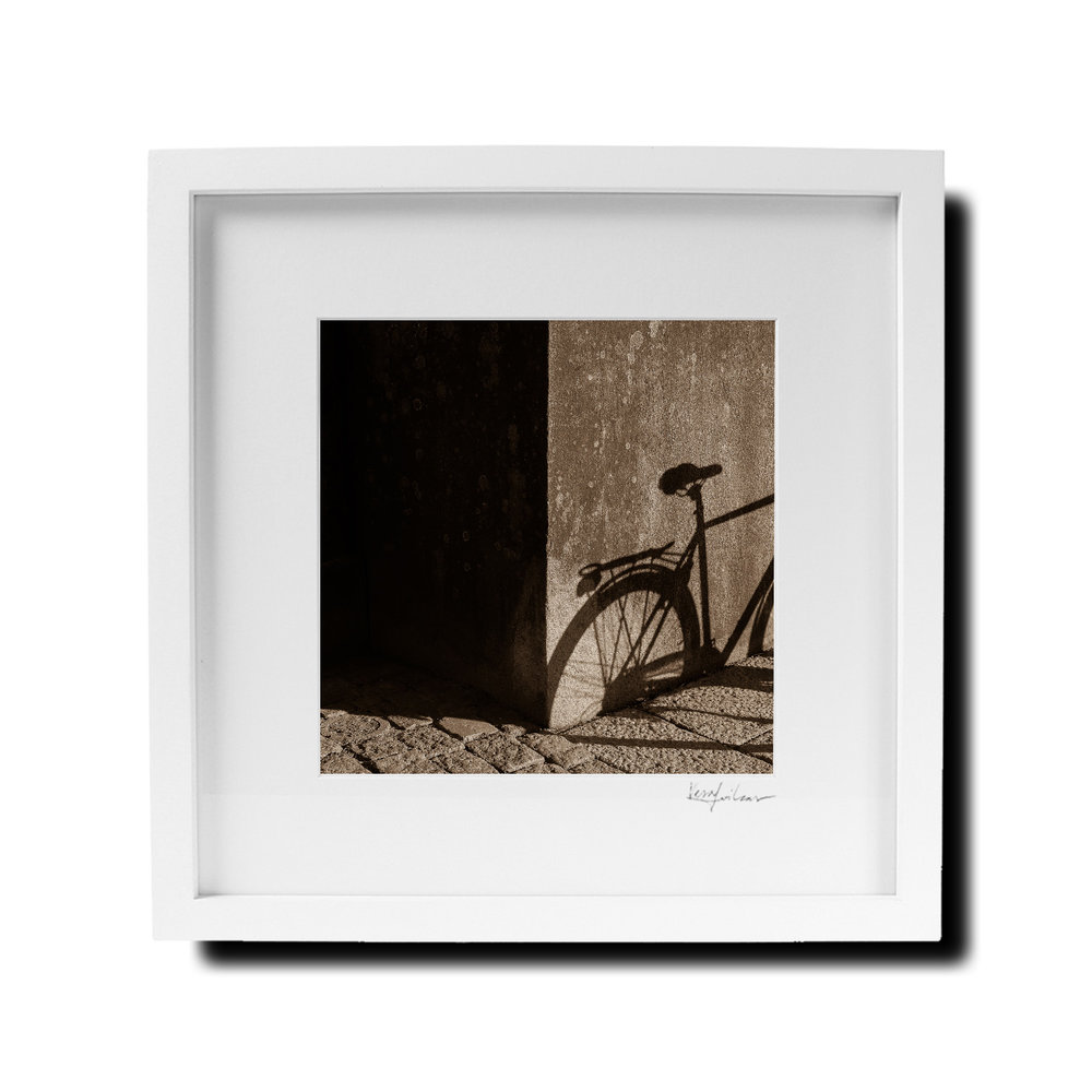🎨 Bicycle Shadow in Cathedral Square, Turku, Finland. First edition print (#1/10) on fine art paper, signed and numbered. White wooden high quality frame is 30 x 30 cm, print itself 19 x 19 cm. AVAILABLE  ONLINE