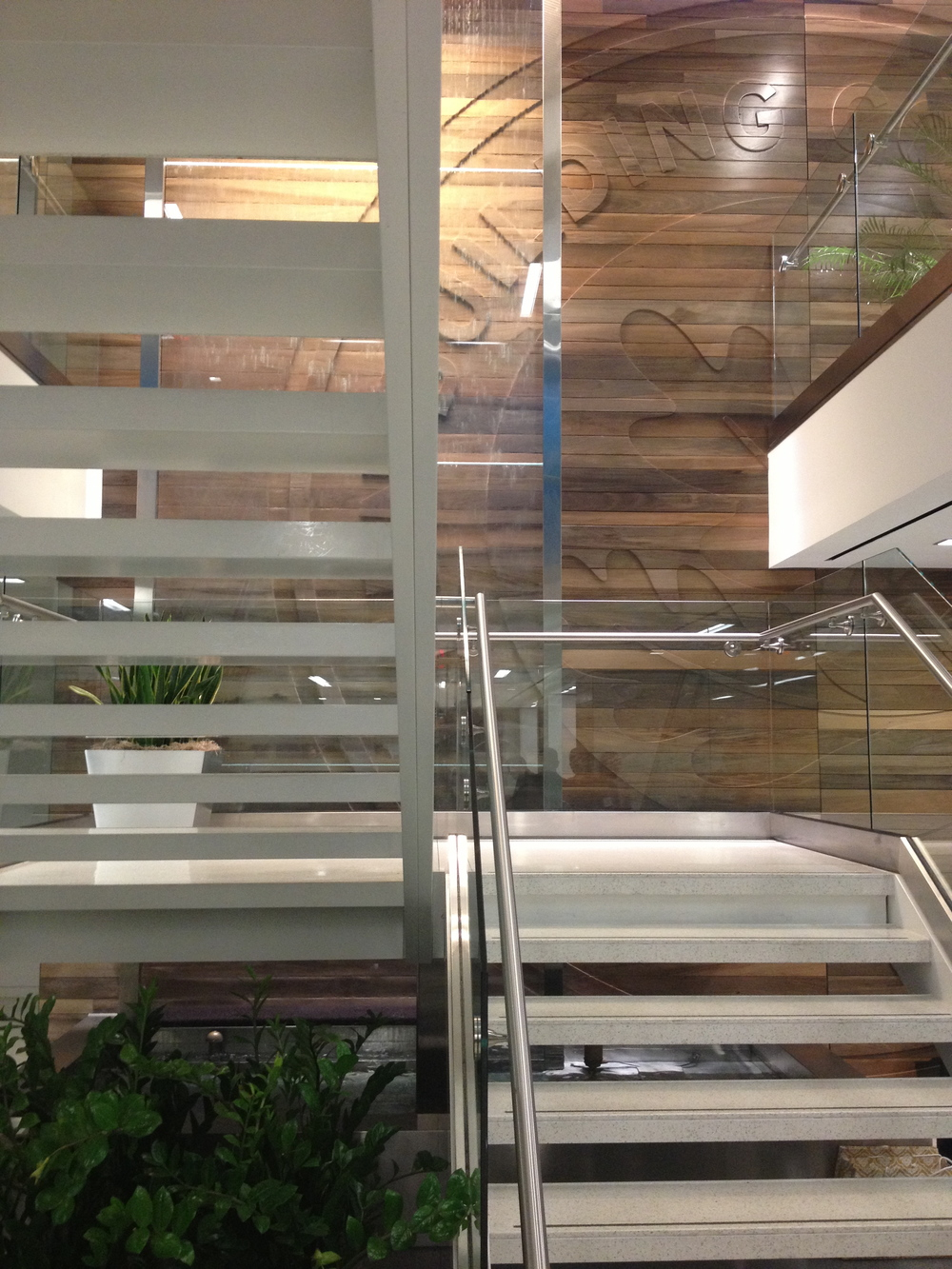 Staircase in U.S. Green Building Council Lobby. Staircase is supported by a thin carbon fiber, almost like a piece of tape, that acts as a support beam. Although you cannot build entire buildings with such material, this was sufficient for the space, and was used in place of putting in a new supporting beam and therefore preserving the visual integrity of the open space. All wooden plants are reclaimed from the bottom of a nearby river and the difference in colors indicated how deep the beam was buried. A waterfall regulates moisture levels and pulls particulates out of the air, improving indoor air quality.