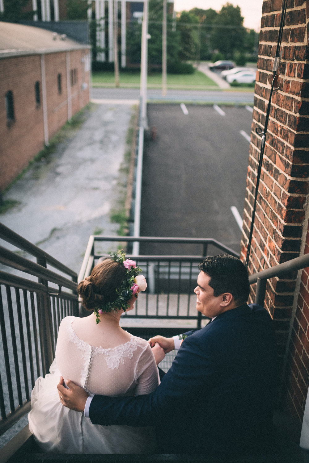 Lauren & Dean sit on the fire escape to take a breather from dancing at their Paducah, Kentucky wedding.