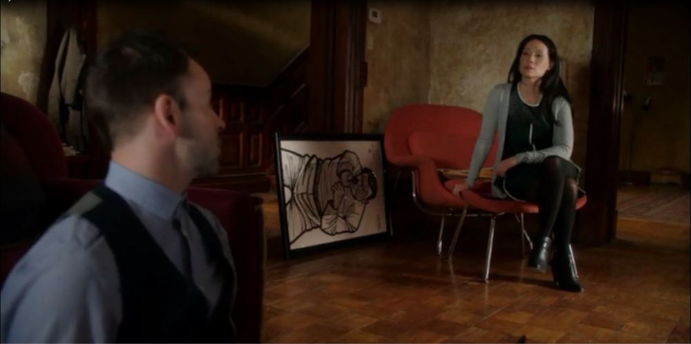 Elementary: Season 2, Episode 18 - Sherlock Holmes's Living room.  Watson has framed a shooting target as a gift for a colleague who overcame an injury to his shooting hand.