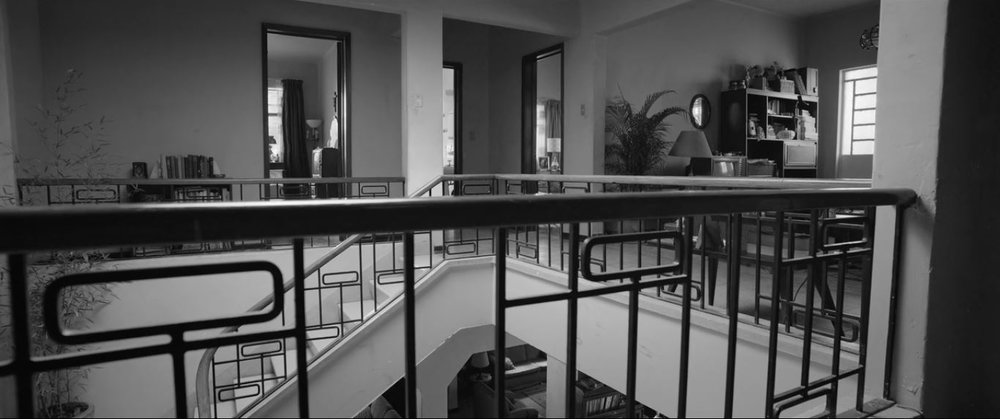 Rome (2018) - Central staircase in  home with too many barrister bookcases.