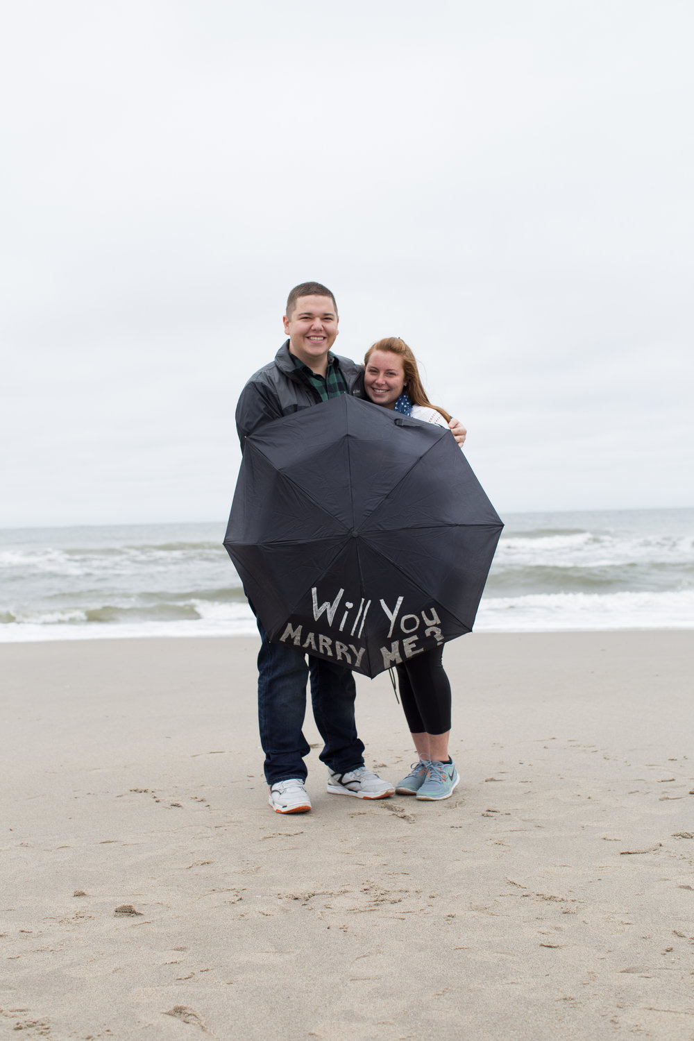 """Tell us about the proposal!: - We live in Rockaway Beach and often take walks along the beach, no matter the season. One cloudy, grey October morning, we headed to the beach for a walk. We started walking towards the shore and it looked like it was going to rain. After commenting on this, Tom announced that he brought an umbrella with him and asked if I wanted to see it. He opened up a black umbrella and in big silver letters read the words """"WILL YOU MARRY ME?"""" I was shocked. It was the most exciting moment of my life! When we got to my parents house to share our big news, every one of our closest friends and family members were there ready to celebrate with us."""