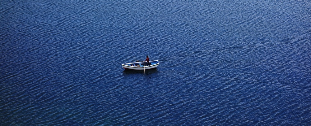 A man rows across Lake Titicaca as seen from Isla Del Sol
