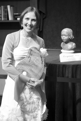 "Mardie Rees poses with her ""Exceptional Merit Award"" (painter's pallet) and her portrait bust, ""La Petite Fleur"""
