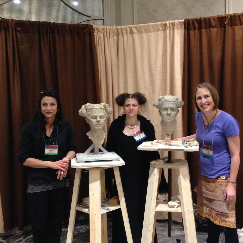 Mardie shows off her finished demo portrait alongside fellow sculptor Alicia Ponzio
