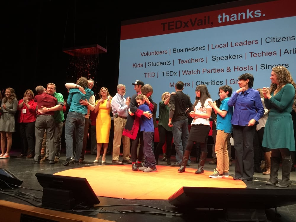 the speakers gathered on stage following the completion of the event. mikela is in the blue blouse.