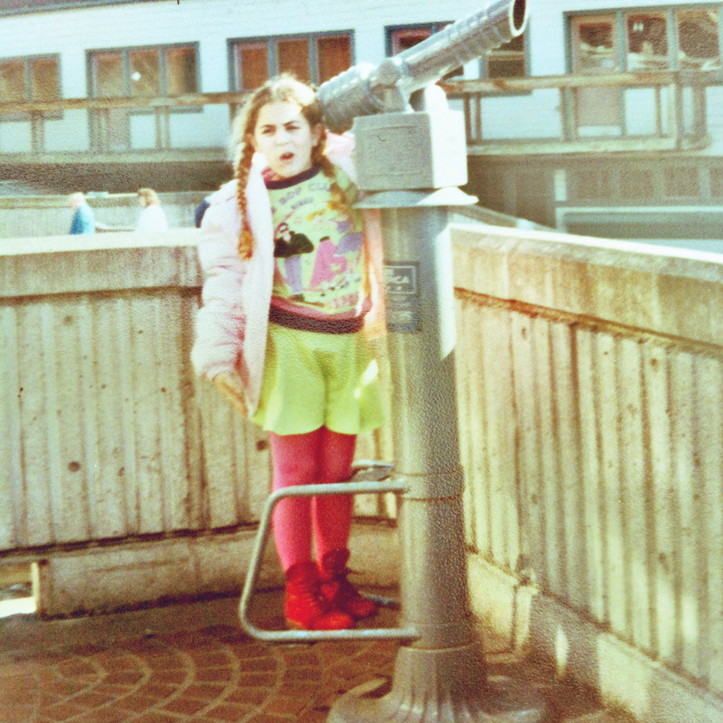 """Myself, 22 years ago.   I am rocking: -Pink puffer jacket with detachable hood, from Sears. -Lime green """"Be Bop Club"""" sweater, with rockabilly dude and bobby soxer characters, from Benetton. -Lime green jersey short culottes, also Benetton. -Fuchsia opaque tights, from JC Penney. -Red suede boots, with plaid details, from Kinney. -Dorothy hairdo, styled by my mother. Parents, this is what happens when you let your kids define their style. That was certainly the height of my iconoclastic style. April 1990."""