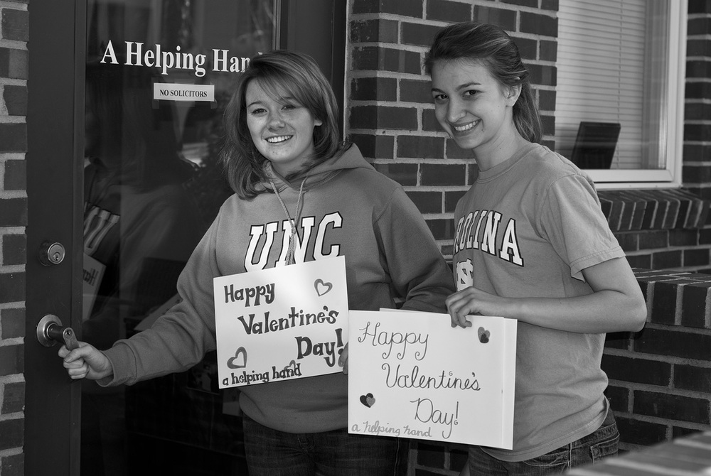 Service-learning Rhetoric and Composition II students Virginia Mayo and Heather Hofmann deliver valentines for the elderly. Likenesses reproduced with permission.