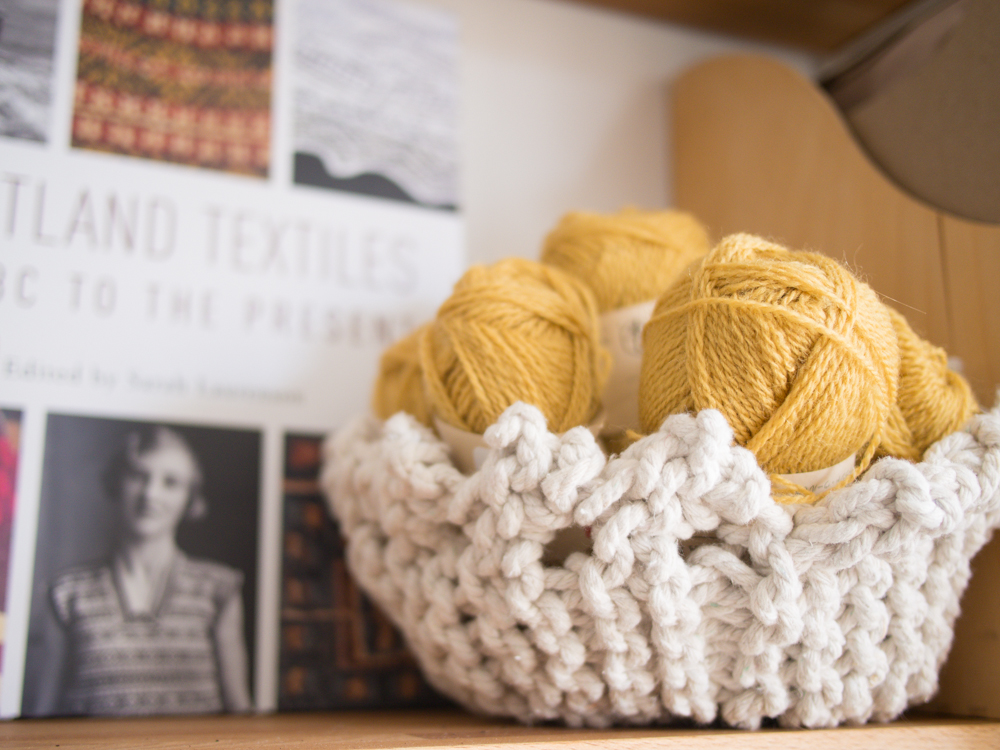 A little knitted basket full of Shetland wool for a future sweater, with the fabulously inspiring Shetland Textiles book behind it.