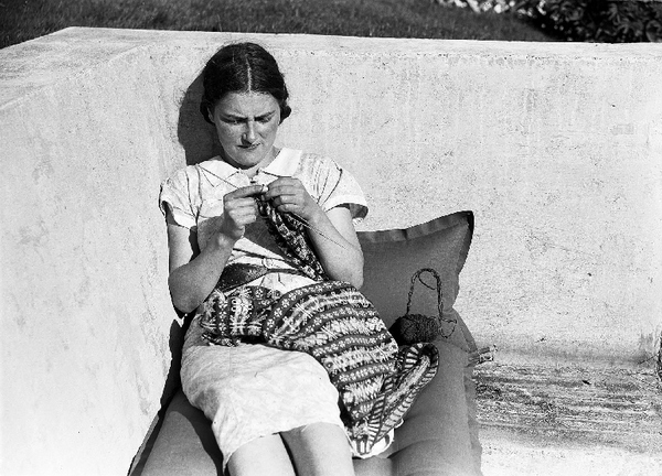 Woman knitting a Fair Isle jumper; she is using a makkin belt.