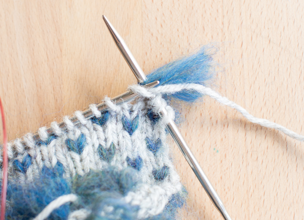 Lay the thrum across the needle, alongside the working yarn.