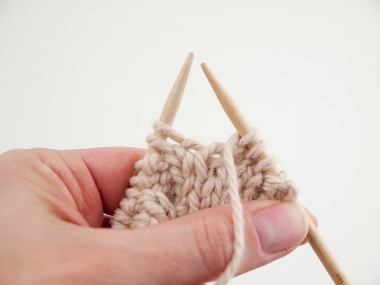 Bring your yarn between the needles to the front.