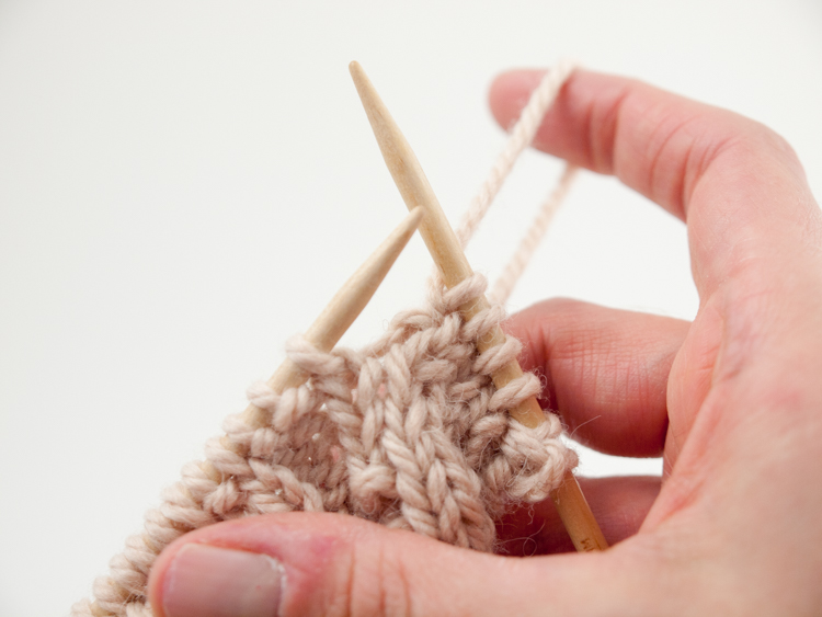 Slip the purl stitch from the left to right needle, and then move the yarn to the back, wrapping the purl stitch as you do so.