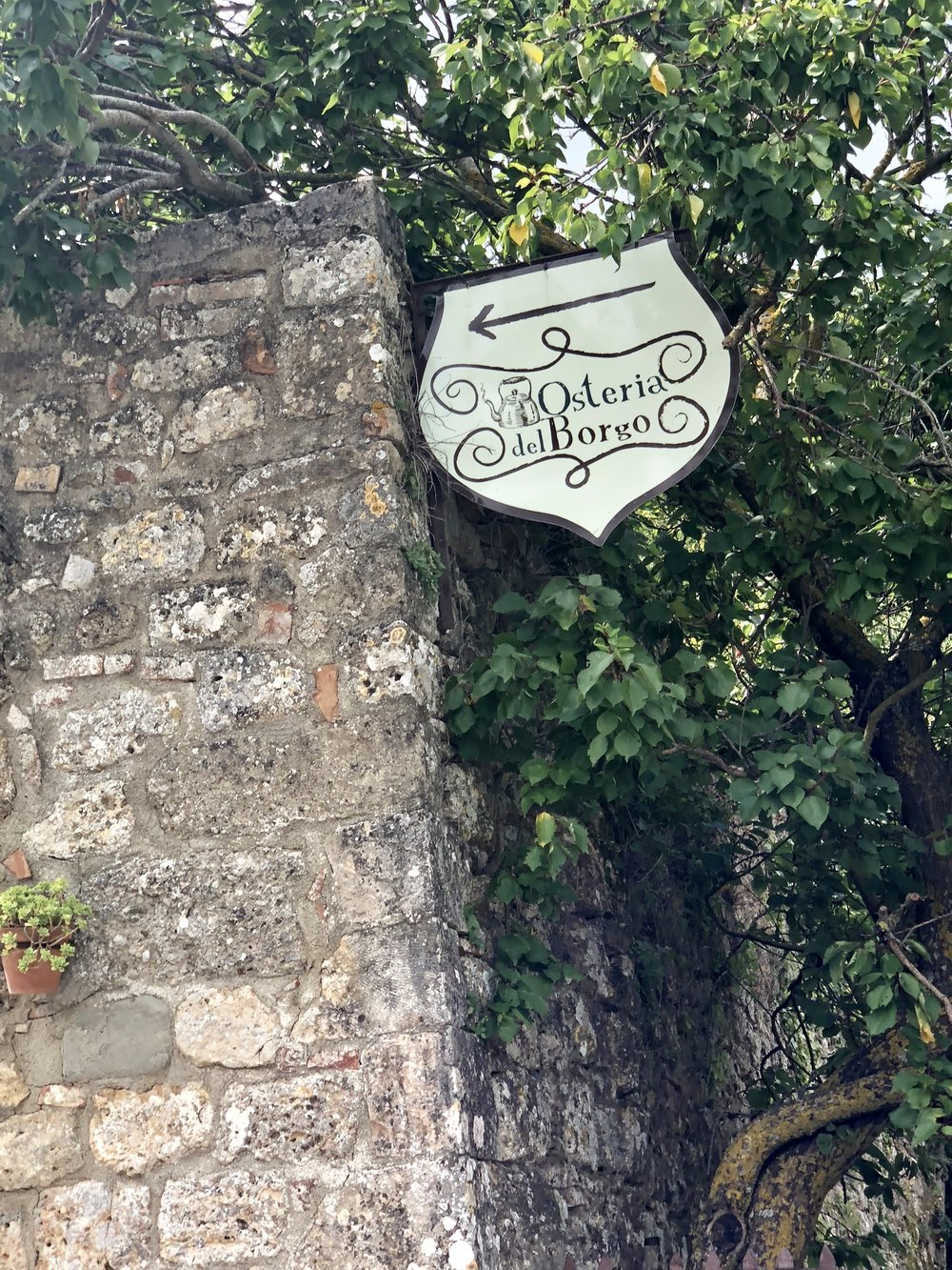 A sign for Osteria del Borgo in the village of Mensano.