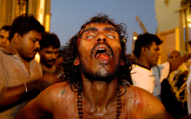 A Tamil man falls into a trance-like state as he performs the Vel Kavadi ritual.  Photo (from the article) by Mark Henley/Panos