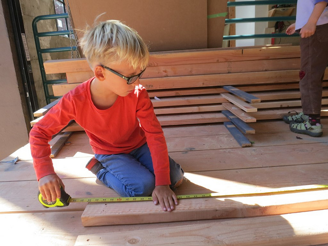 Leo measures a piece to see if it's long enough to use as a wall stud.