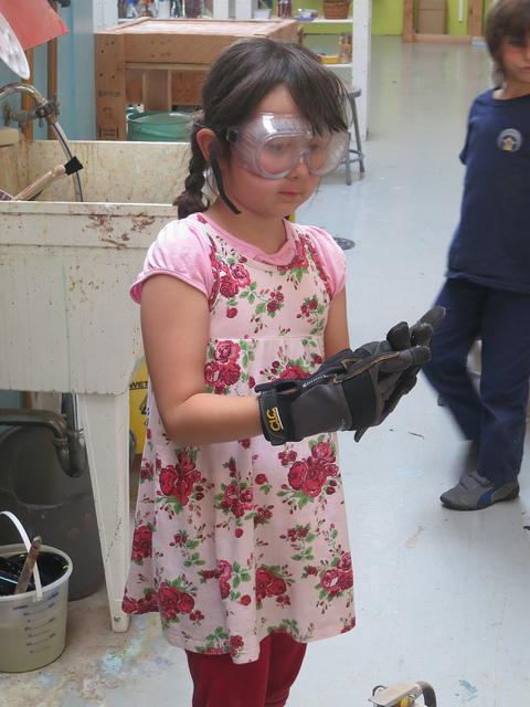 Isabella, in goggles and gloves, is ready to short the circuit of a 12-volt battery.