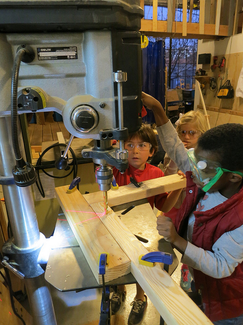 Jah-Amiel and Noah use the drill press to make precise holes for their rolling cart.