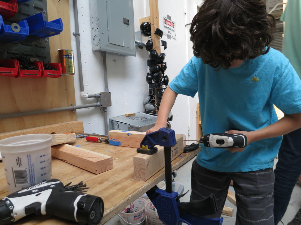On the final minutes before clean-upo, Elijah makes a brace for the full size gutters. It will be one of over 30 braces!