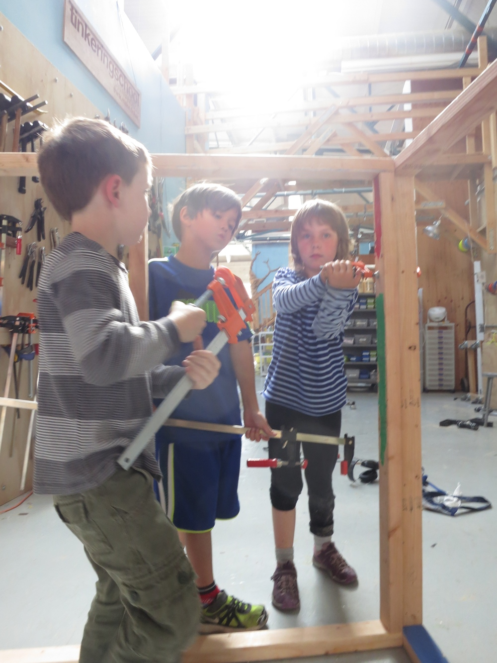 Evan, Dash and Scarlett clamp two walls together.