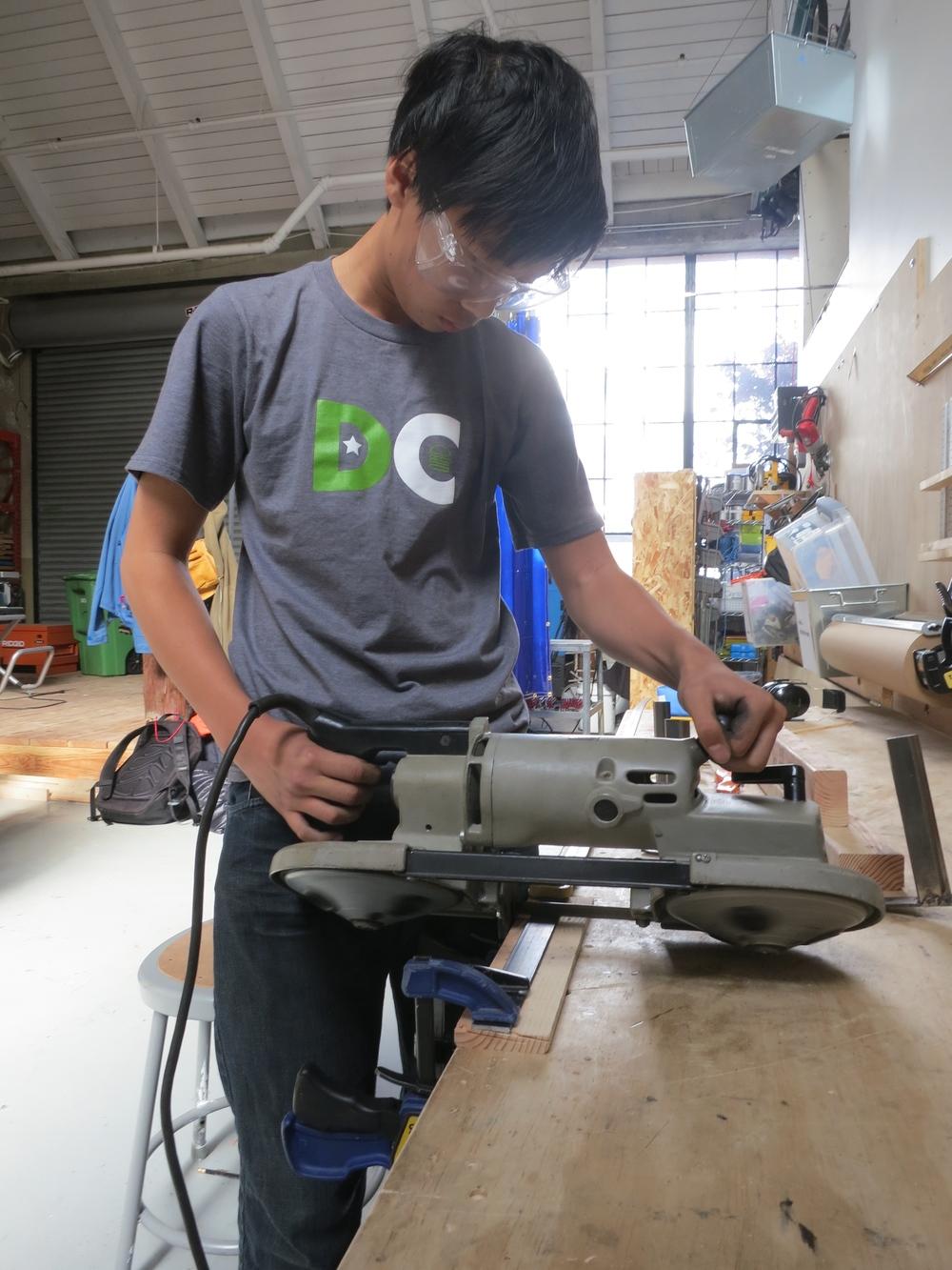 Panu cuts flat bar steel for shelf brackets.
