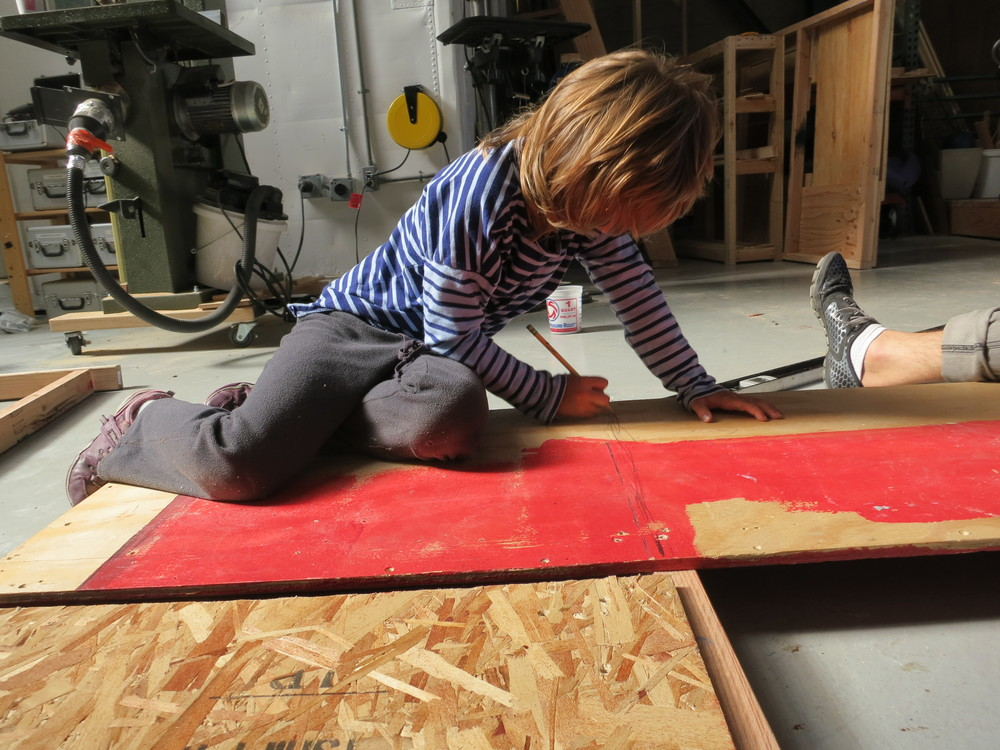 Scarlett marks the bottom plate of the framing, so she'll know where to put screws in the plywood.