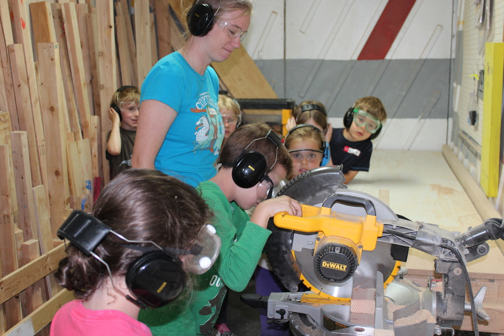 Collaborator Lindsay helps kids use the chop saw safely.