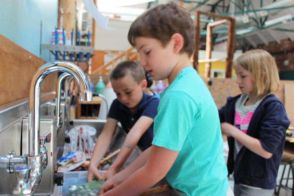 Fitz, Phoebe and Alex wash paintbrushes.