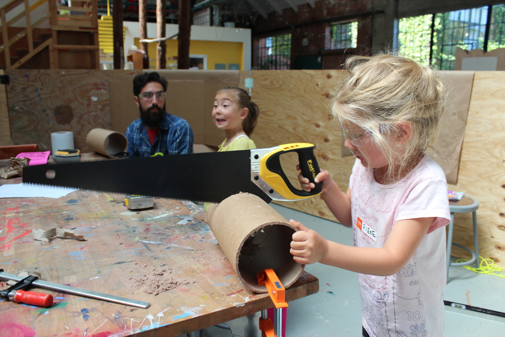 Pieke cuts moon boot parts with her hand saw skills, while Maisy stabilizes for her.