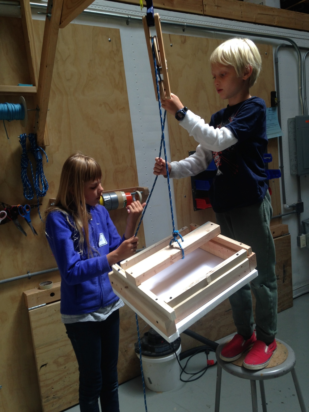Emilia and Sebastian found a wooden pulley they liked, and built a dumbwaiter.