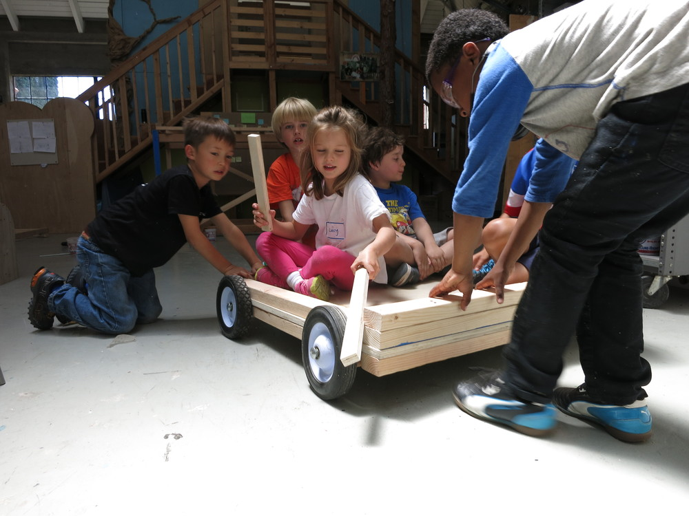 Kevin, Henry and Kielson pull Lulu and James on a cart they made this morning.