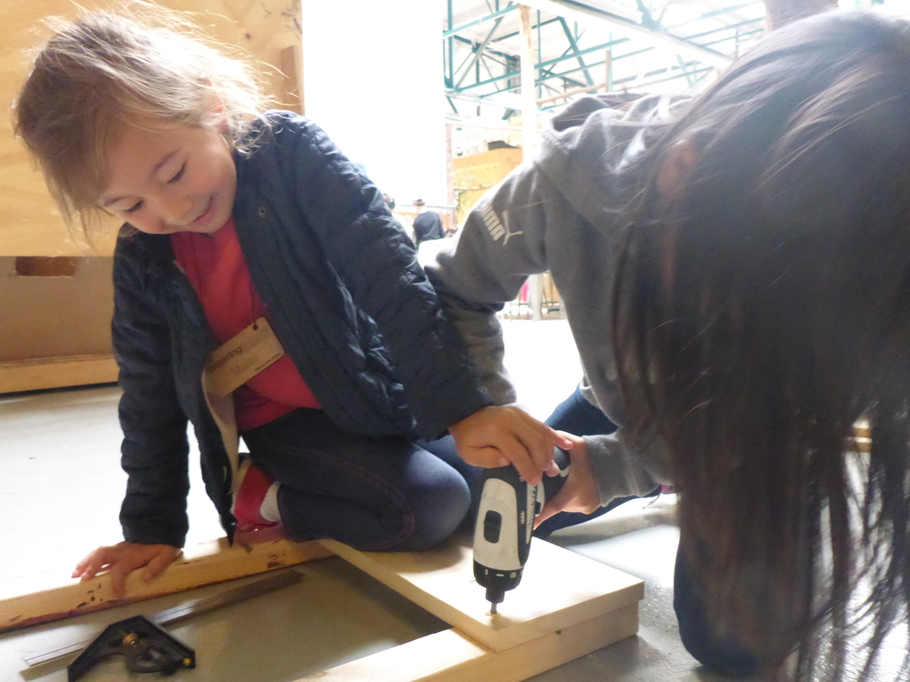 In this picture, one six-year-old helps another six-year-old use a power drill. They met this week. They are building a a train shaped like a dragon together. They are friends, for they are building together. We are so proud of these kids!