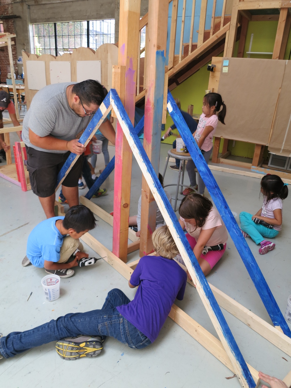Micah, Thomas, Mason,Chelsea, Sophia and super-volunteer Jhonny work on the fulcrum of a giant Scales of Justice.