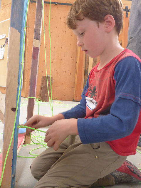 Auden practices the square knot he just learned to attach the laser cord to the Maze!
