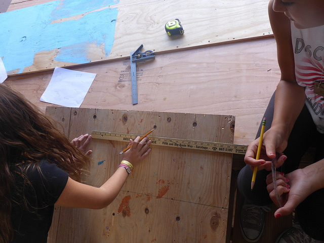 Elizabeth, Katherine, and Clem do some complicated measuring to get the angle of the domino stairs just right.